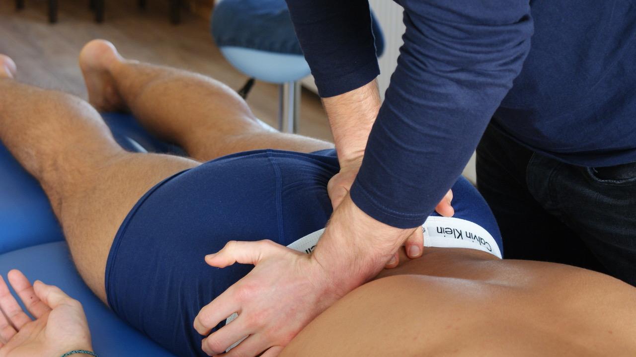 Manueel Therapeut In Heerenveen Doet Een Behandeling Aan De Lage Rug Van Iemand Met Rugklachten